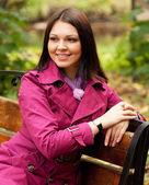 Girl on bench in autumn park — Stock Photo