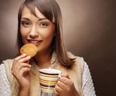 Young woman with coffee and cookies — Stock Photo