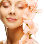 Fresh face with gladiolus flowers in her hands — Stock Photo