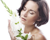Woman with gladiolus flowers — Stock Photo