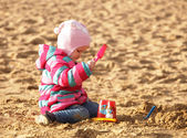 Girl playing with sand at the autumn beach — Stock Photo