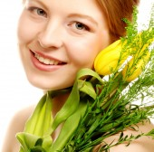 Young smiling woman with yellow tulips — Zdjęcie stockowe