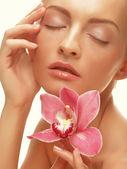 Orkide çiçek ile güzel kız. — Stok fotoğraf