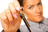 Woman holding up a key — Stock Photo