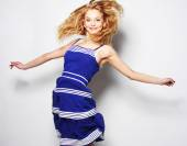 Young happy woman in blue dress jumping — Stock Photo