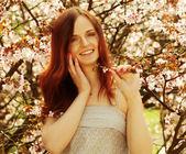 Szczęśliwa młoda kobieta w ogród kwiaty wiosną — Zdjęcie stockowe