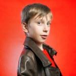 Beautiful stylish blond boy wearing leather coat posing over red background — Stock Photo #53499037