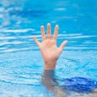 A hand of a drowning person stretching out of the water in a swimming pool asking for help. Stress concept. — Stock Photo #53499853