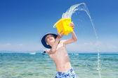 滑稽的小男孩,与巴拿马在海里扔一黄色玩具桶水玩 — 图库照片