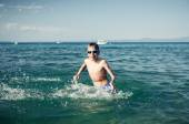 Funny little child playing in the sea splashing water laughing. Summer vacation concept. — Stock Photo