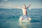 Funny little child playing in the sea splashing water and jumping. Summer vacation concept. — Stock Photo