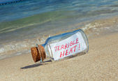"Message in a bottle ""Terrible heat"". Creative summer break concept. — Stock Photo"
