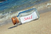 """Message in a vintage bottle """"Sale"""" on beach. Creative marketing concept. — Stock Photo"""