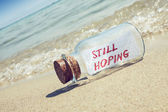 "Message in a bottle ""Still hoping"" on sandy beach. Creative hope and faith concept. — Stock Photo"