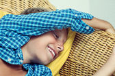 Beautiful funny little child lying on cozy wicker sofa dreaming and laughing. — Stock Photo