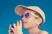 Beautiful child wearing stylish sunglasses holding camera — Stockfoto