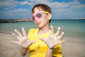 Cute child wearing colorful sunglasses on beach showing hands — Foto Stock