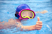 Child wearing a colorful swimming mask swimming in an open-air swimming pool — 图库照片