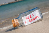 "Vacation and stress concept. Vintage bottle with text message ""need a break"" lying on a sandy beach — Stock Photo"