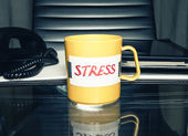 "Coffee mug with a message ""stress"" on an office table with business accessories. Stress and depression concept. — Foto Stock"