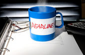 """Creative business concept. A coffee cup with a message """"deadline"""" on an office table — Stock Photo"""