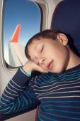 Beautiful child travelling by airplane sleeping in a seat near a window — Foto Stock