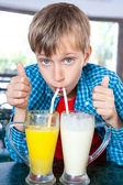 Lindo niño gracioso bebiendo cócteles de frutas de un dos grandes vasos con pajitas. concepto creativo bebida. — Foto de Stock