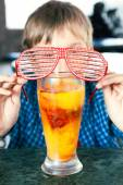 Funny child with party sunglasses drinking a fruit cocktail from a big glass — Stock Photo