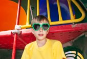 Beautiful child wearing funny sunglasses playing on playground in summer — Stock Photo