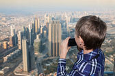 Little boy watching at a big city from above holding a camera taking photo — Stock Photo