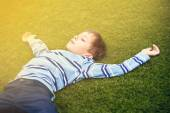 Beautiful child lying on green grass in a park with his eyes closed in golden sunshine — Stock Photo