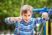 Beautiful happy child swinging on a playground in a sunny park and smiling. — Stock Photo