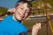 Beautiful happy boy swinging on a playground in a sunny park and laughing — Stock Photo
