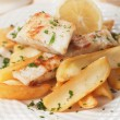 Cod fish steak with fried potato and lemon — Stock Photo #59526411