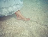 The foot of the bride touches water in the sea,with a retro effect — Stock Photo