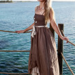 The young beautiful woman  on a wooden platform over  the sea — Stock Photo #57478955