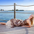 The young beautiful woman on a wooden platform over the sea — Stock Photo #57478995