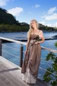 熱帯の島で木製の橋の上に座って長いドレスを着た美しい女性 — ストック写真