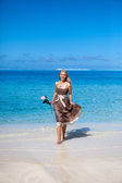 The beautiful woman with a rose runs on the edge of the sea on a beach. Polynesia — Stock Photo