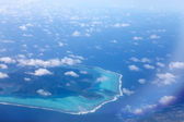 Polynesia. The atoll in ocean through clouds. Aerial view — Stock Photo
