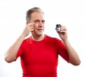 The mature man has reflected on application of a man's cream against wrinkle — Stock Photo