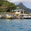 Hut at the foot of the mountain on the seashore and boat pier — Stock Photo #65393971