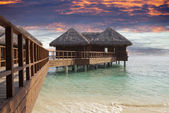 Lodges over water at the time sunset. Maldives — Stock Photo