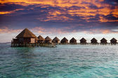 Lodges over water at the time sunset. Maldives — Stockfoto