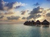 Houses over the sea at sunrise. Maldives — Stock Photo
