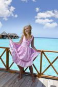 Young beautiful girl stands in pink sundress on sundeck of villa on water, Maldives — Stock Photo