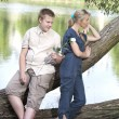 Young guy and girl on the nature near lake, reconciliation after quarrel — Stock Photo #69736217
