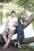 Young guy and girl on the nature near lake, reconciliation after quarrel — Stock Photo
