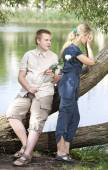 Young guy and girl on the nature near lake, reconciliation after quarre — Stock Photo