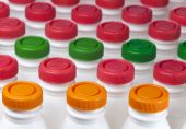 Dairy products bottles with bright covers — Stock Photo